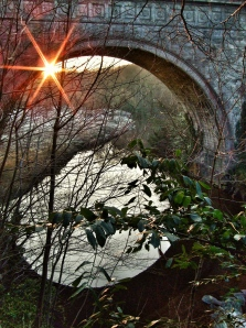 Round sunburst framed by Kings Bridge